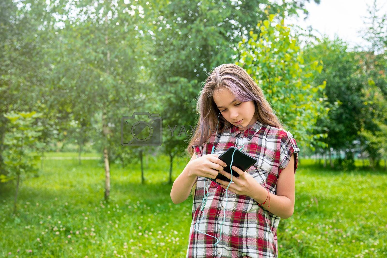 A young girl of 15 years old Caucasian appearance wary with apprehension looks into her mobile phone on the lawn in the park on a summer day. The girl is dressed in a plaid shirt and jeans.