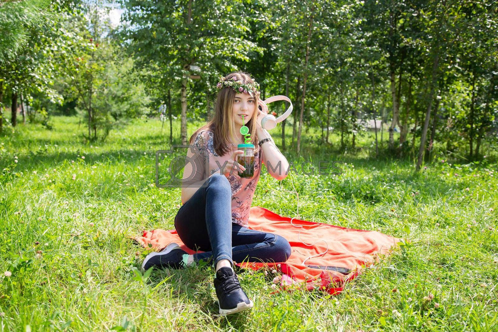 A young girl 20 years old Caucasian appearance listens to music while sitting on the lawn in the park on a summer day. The girl is dressed in a T-shirt and jeans and a wreath of wildflowers.