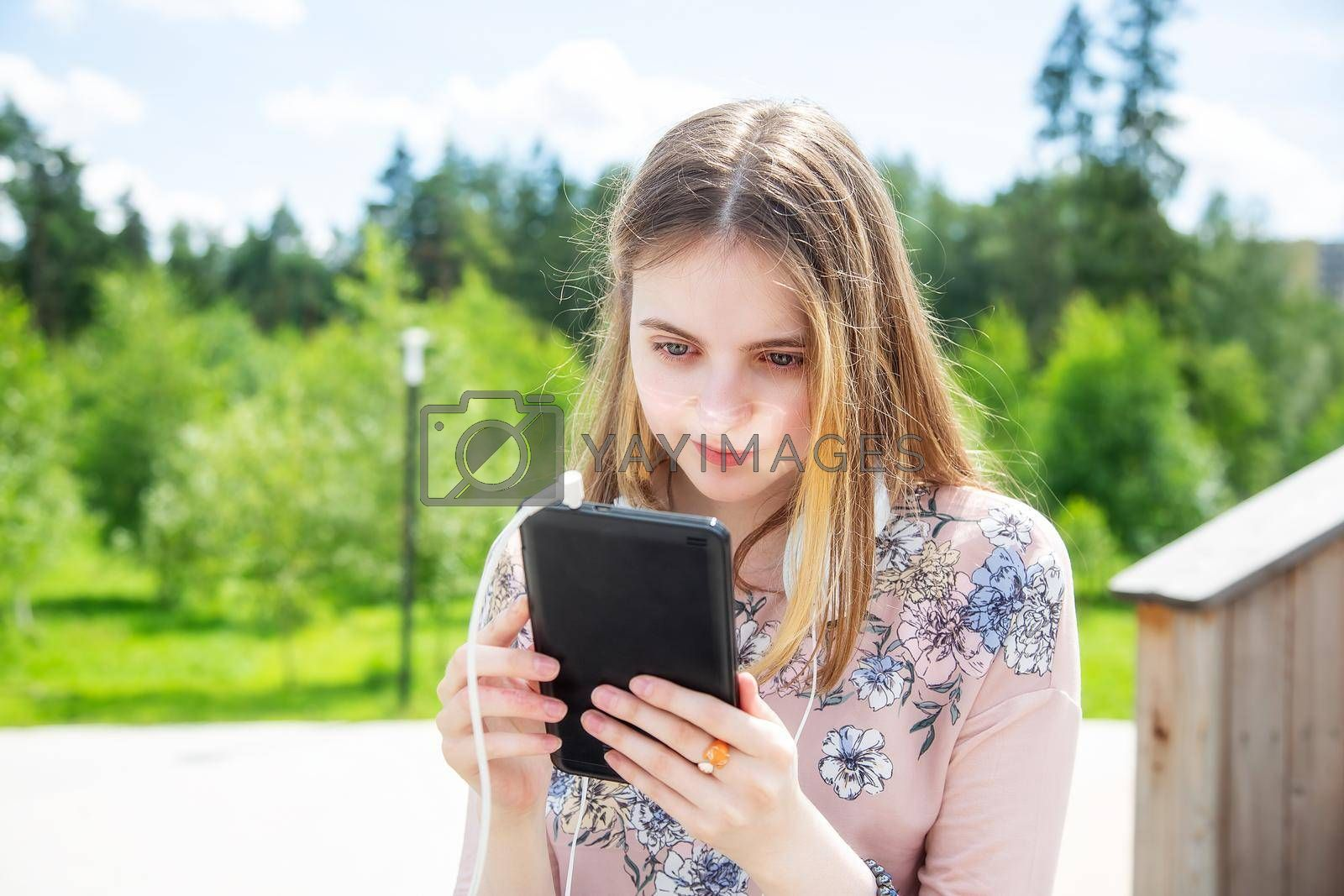 A young girl 20 years old Caucasian appearance looks into her mobile phone, writes a text message while sitting on a wooden podium in the park on a summer day.The girl is dressed in a floral T-shirt