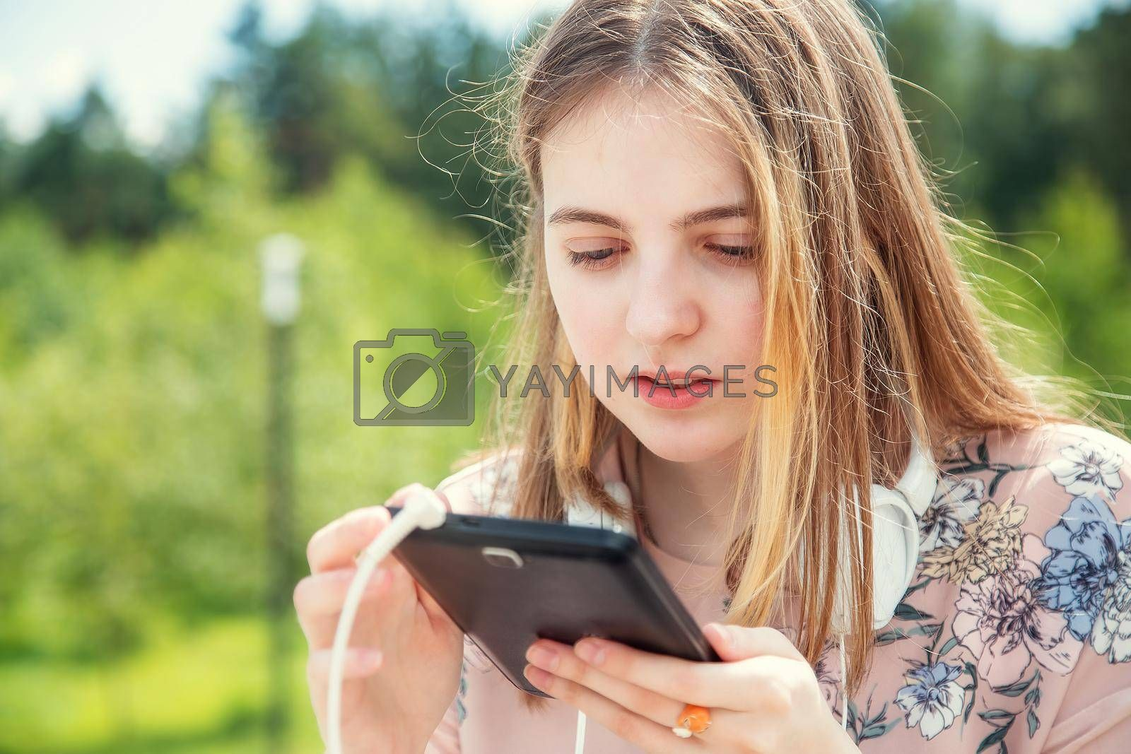 A young girl makes a video call on her mobile phone while sitting in the park by galinasharapova