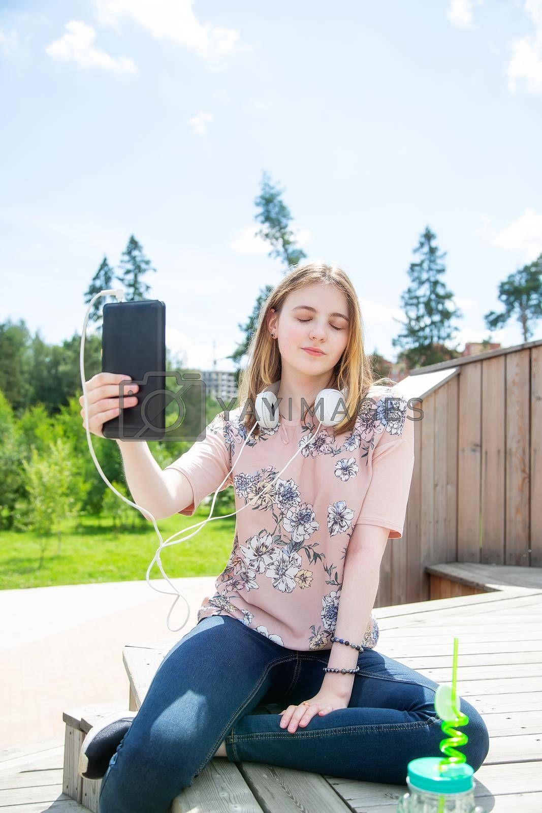 A young girl of 20 years old Caucasian appearance makes a selfie on her mobile phone while sitting on a wooden podium in the park on a summer day.The girl is dressed in a floral T-shirt and jeans,