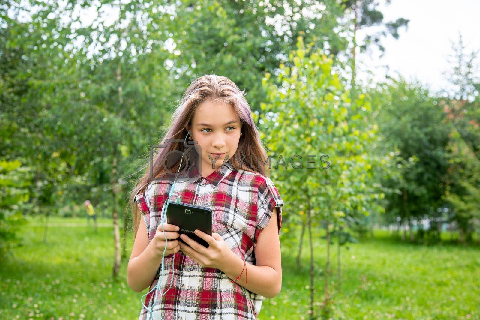 A young girl of 15 years old looks around and holds a mobile phone in the park by galinasharapova