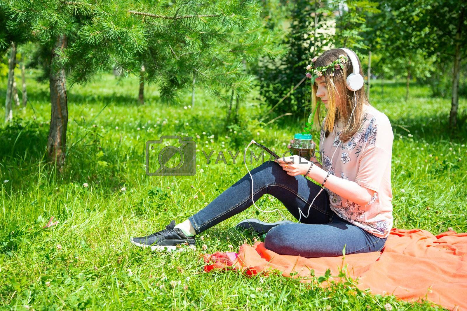 A young girl 20 years old Caucasian appearance looks into her mobile phone, writes a text message while sitting on the lawn in the park on a summer day. The girl is dressed in a floral T-shirt