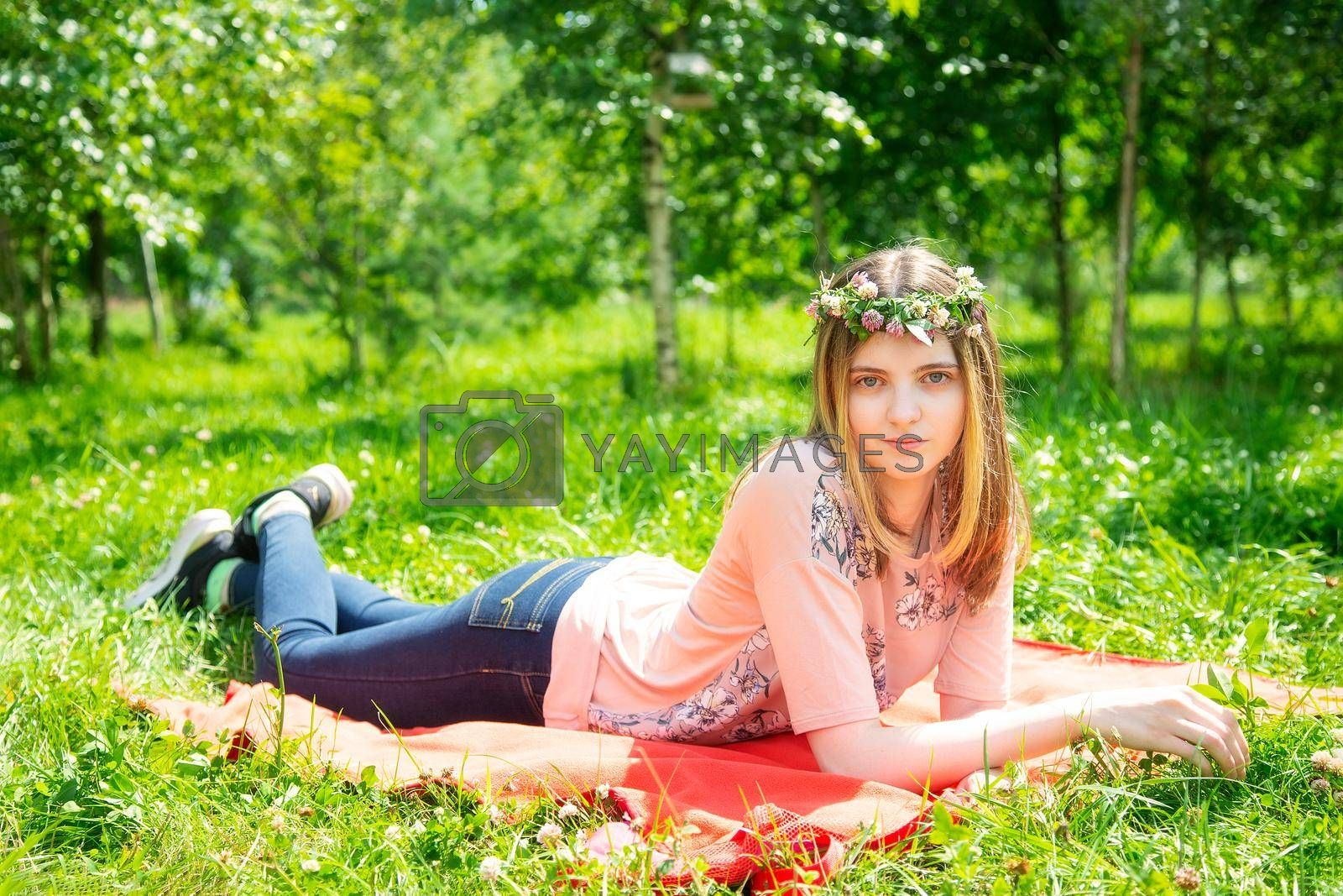Young girl 20 years old Caucasian appearance smiling looking at the camera while lying on the lawn in the park on a summer day. The girl is dressed in a T-shirt and jeans and a wreath of wildflowers.