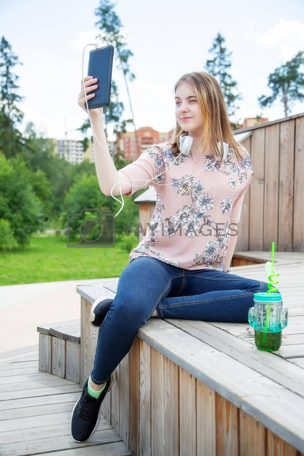 A young girl makes a selfie on her mobile phone while sitting in the park by galinasharapova