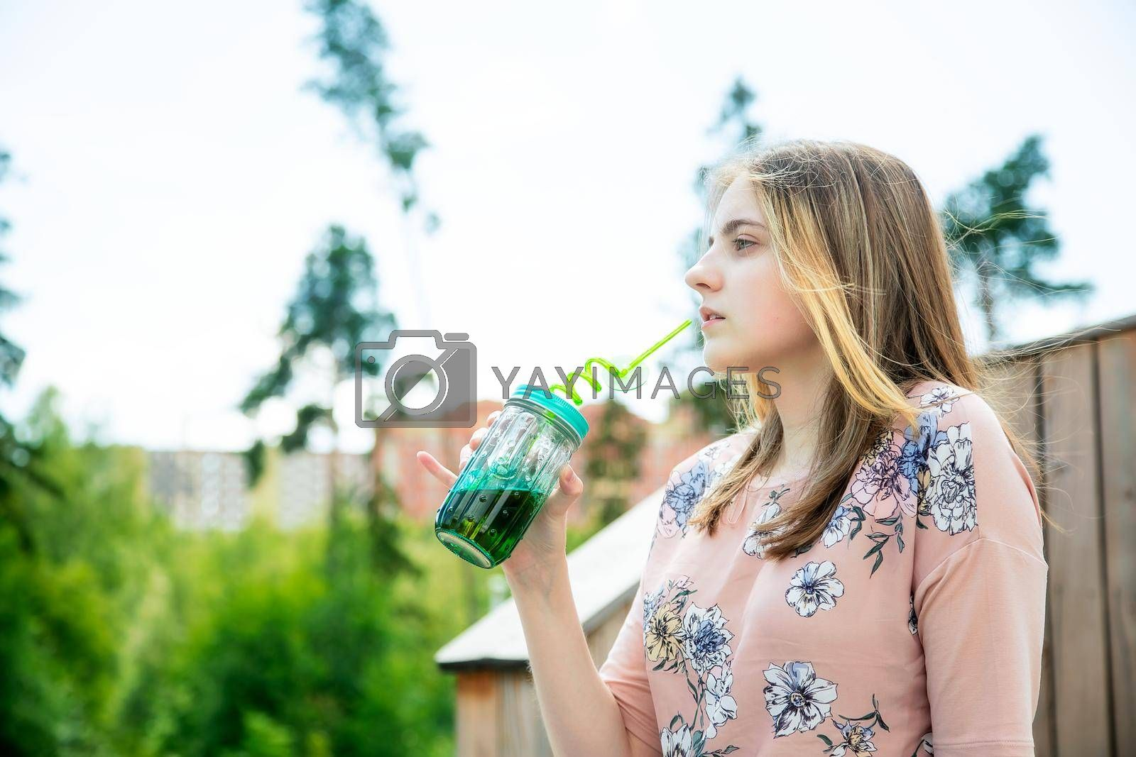 A young girl enjoys the sun and weather and drinks smoothies from a large glass by galinasharapova