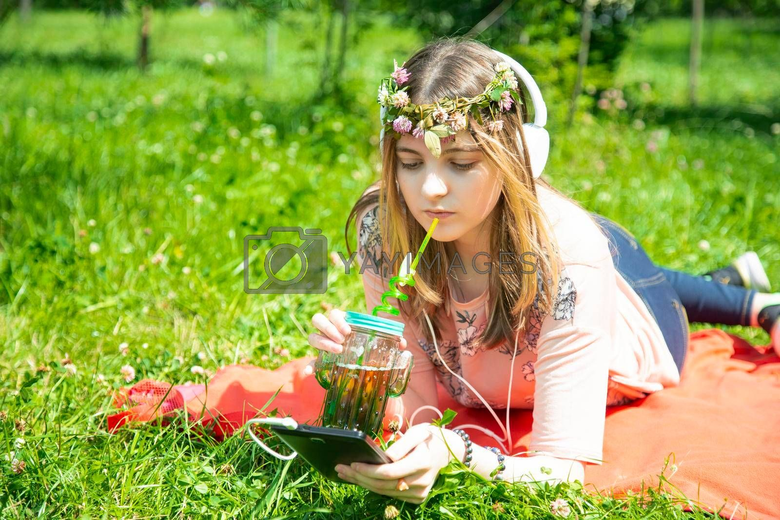 A young girl listens to music on her mobile phone and drinks smoothies in park by galinasharapova