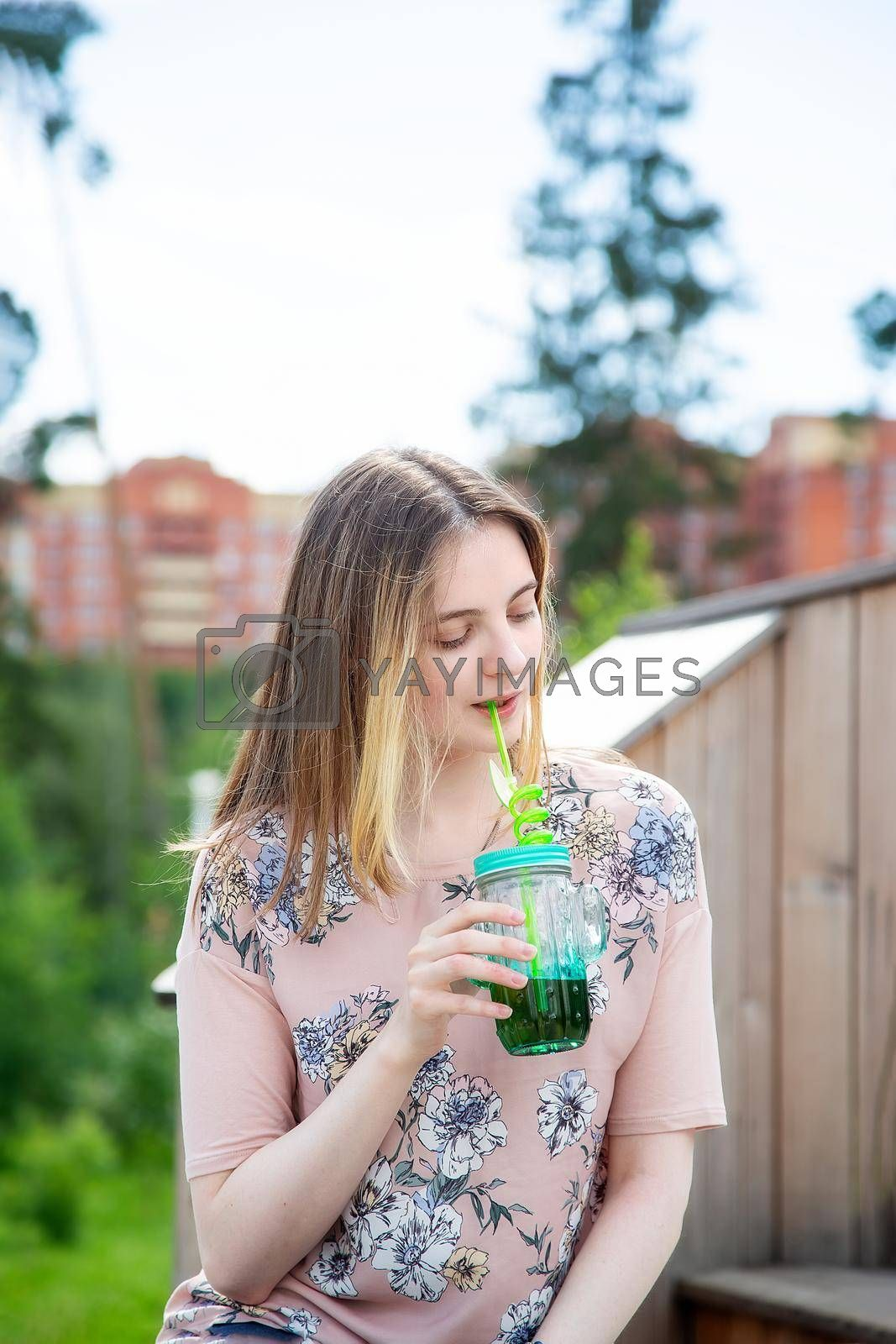 A young girl of 20 years old Caucasian appearance enjoys the sun and weather and drinks smoothies from a large glass while sitting on a wooden podium in the park on a summer day.