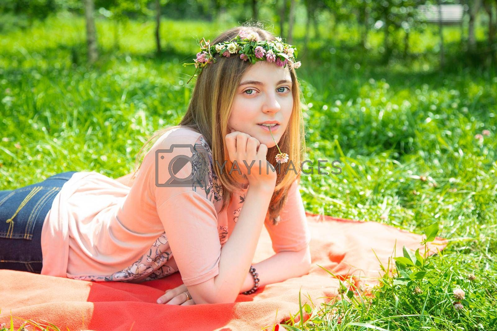 Young girl smiling looking at the camera while lying on the lawn in the park by galinasharapova