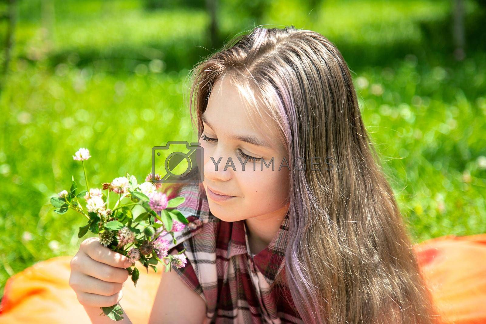 A young girl of 15 years old Caucasian appearance enjoys the sun and the weather and a bouquet of wild flowers lying on the lawn in the park on a summer day. The girl is dressed in a plaid shirt