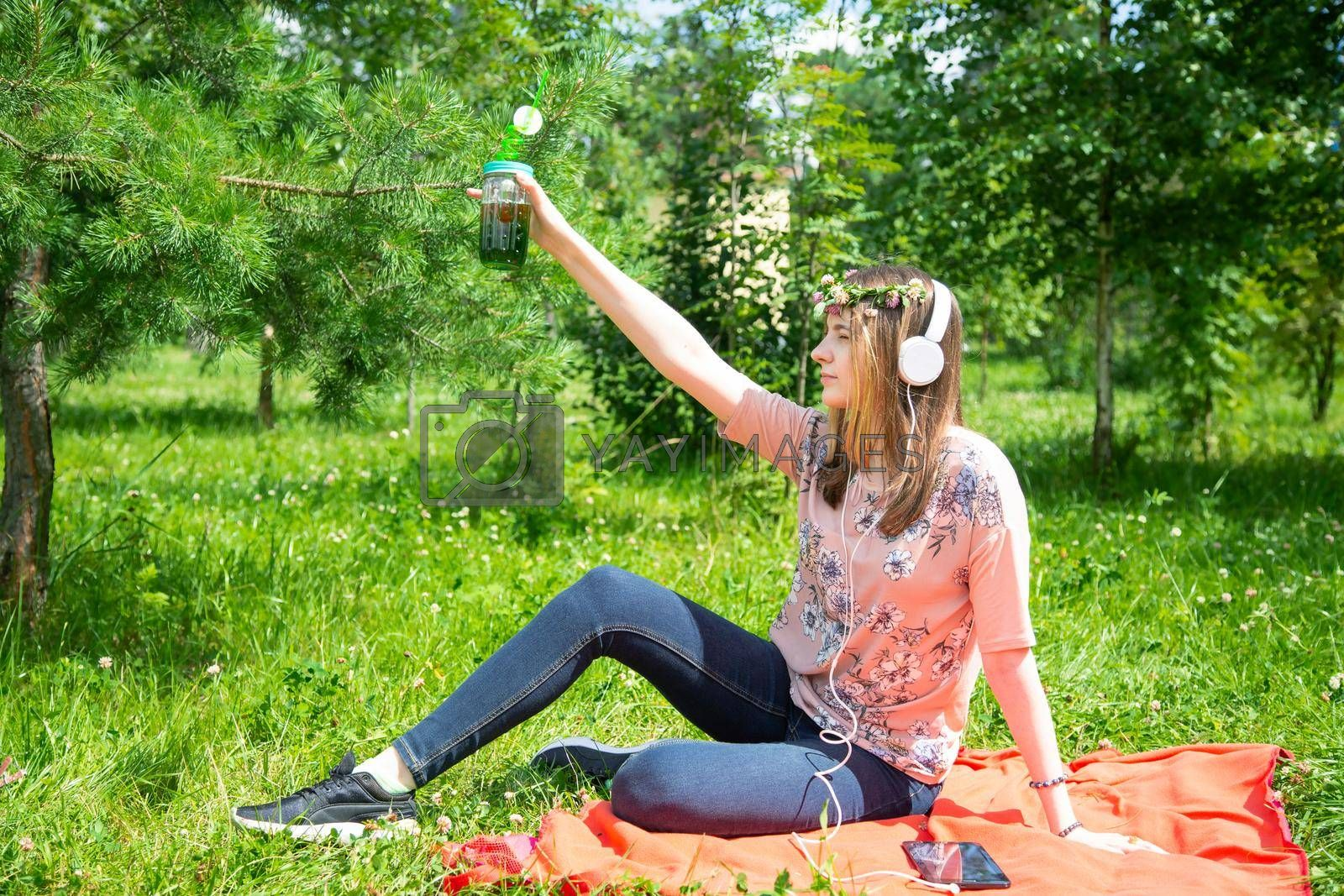 A young girl of 20 years old Caucasian appearance makes a selfie on her mobile phone while sitting on the lawn in the park on a summer day. The girl is dressed in a floral T-shirt and jeans