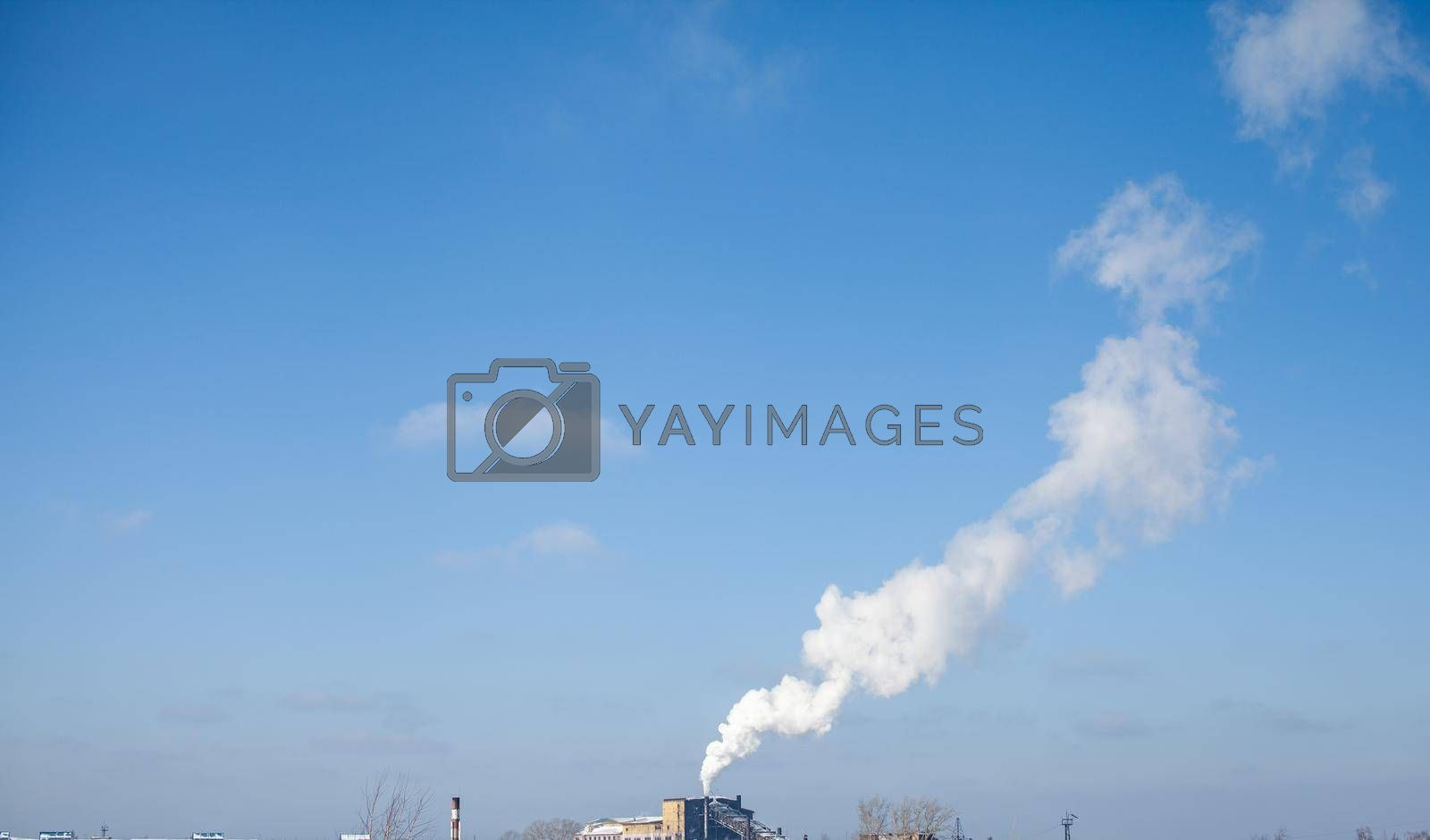 White thick smoke from the boiler room chimney. Smoke against the blue sky. Air pollution. Heating of the city. Industrial zone.