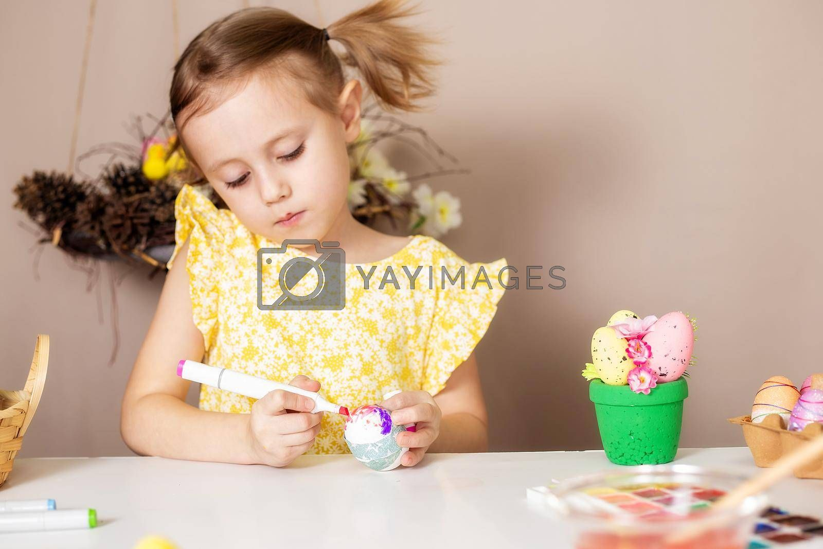 A small Caucasian girl of 5 years old paints eggs with special markers for the Christian spring holiday of Easter. The girl is dressed in a yellow floral dress and has ponytails.
