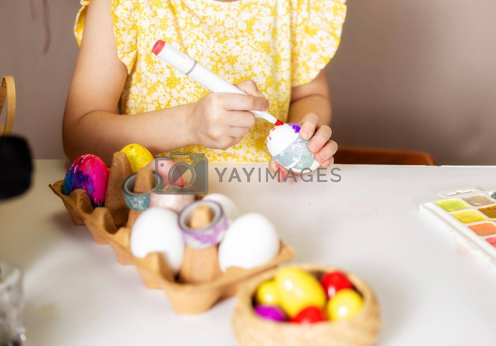 Close-up on the hands of a small girl 5 years old paints eggs with markers by galinasharapova