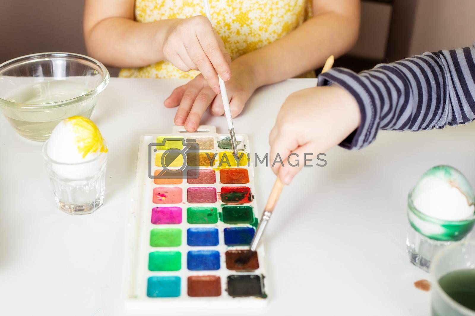 Close-up on the hands of little Caucasian children who paint eggs with special paints for the Christian spring holiday of Easter.