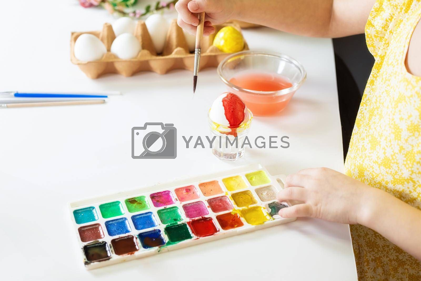 Close-up on the hands of a small girl 5 years old paints eggs with water paints by galinasharapova