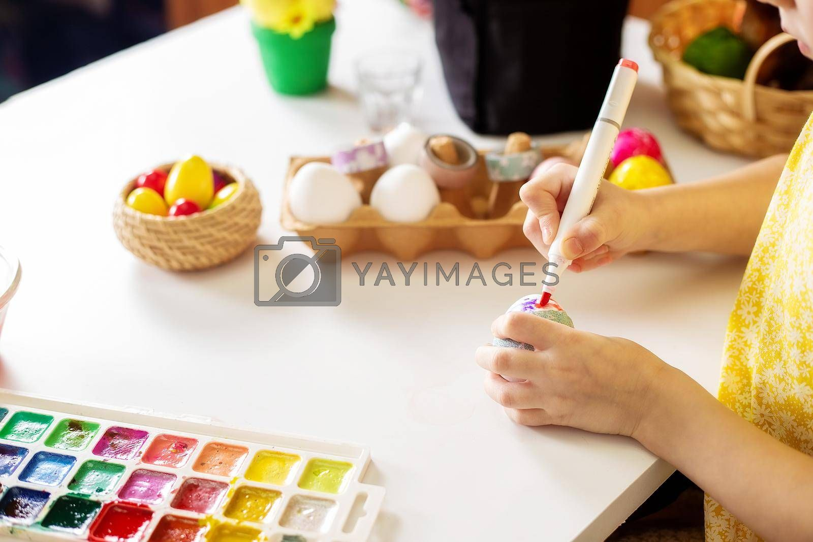 A close-up on the hands of a small girl 5 years old paints eggs with markers by galinasharapova