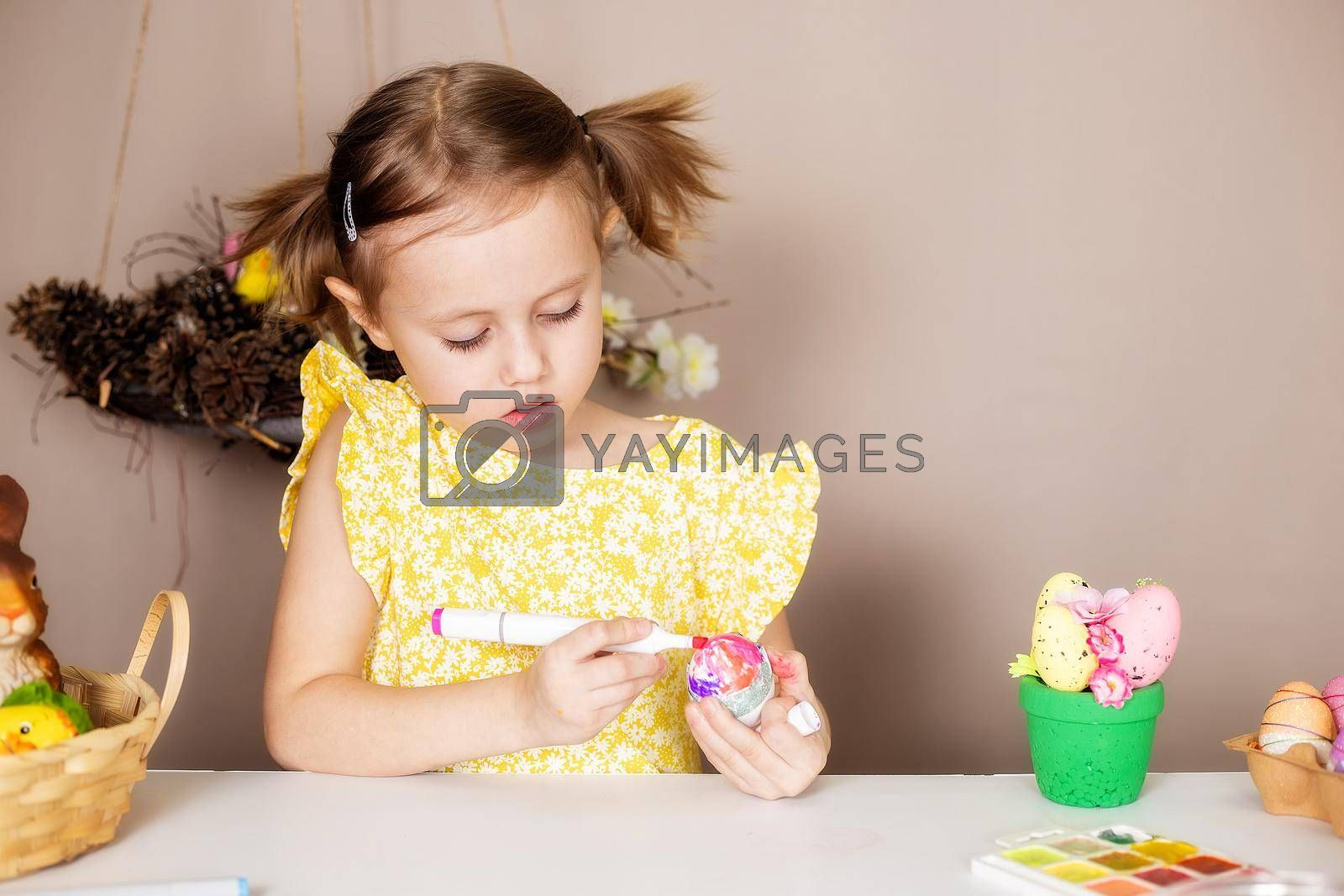 Small Caucasian girl of 5 years old paints eggs with special markers for Easter. by galinasharapova