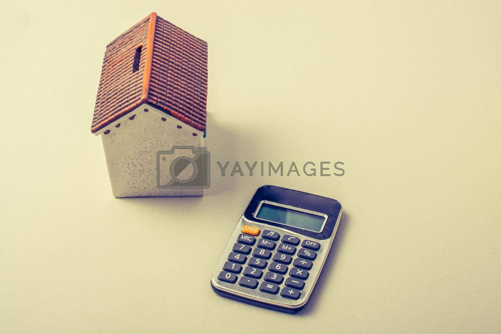 Model house and calculator placed on white background