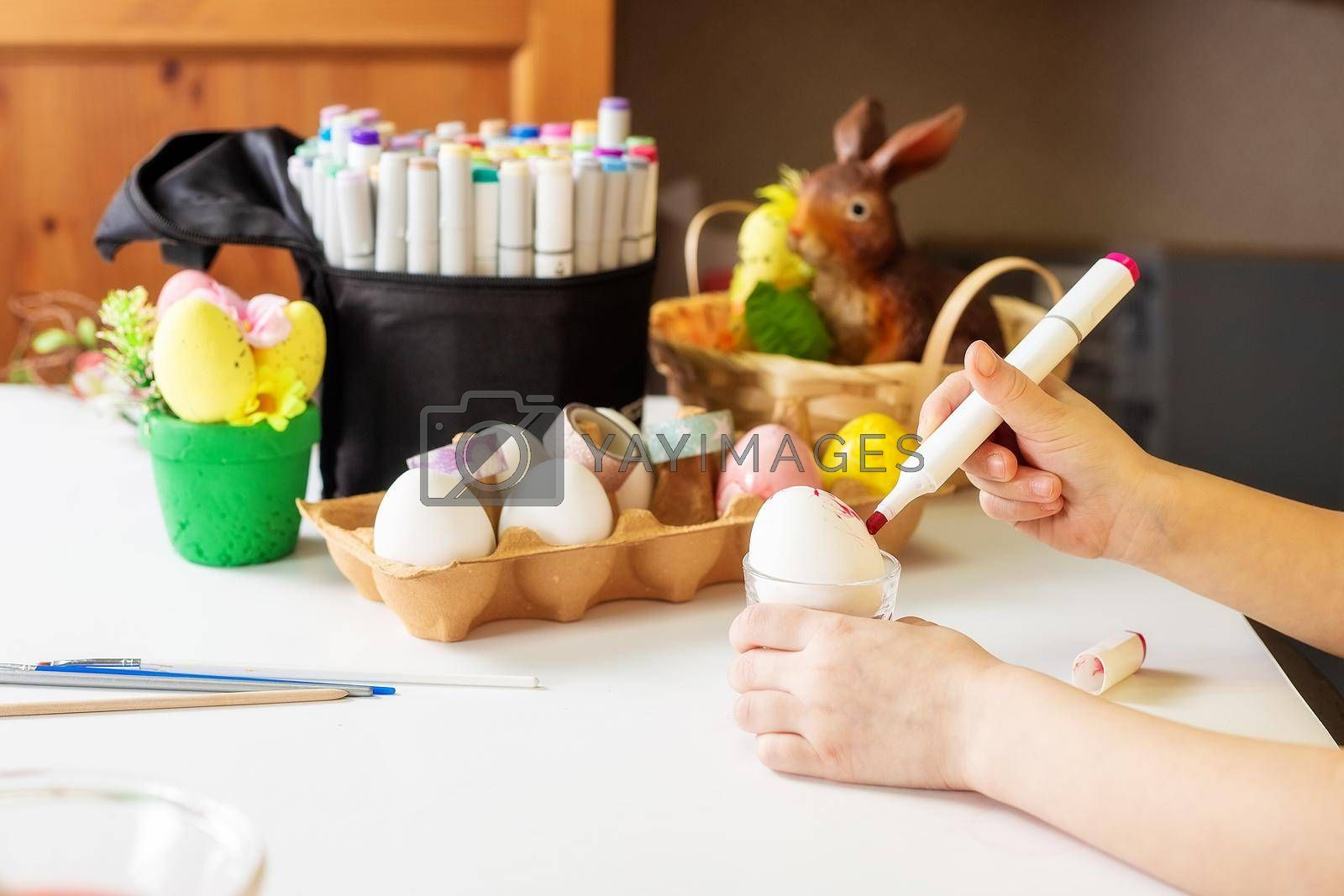 A close-up on the hands of a small Caucasian girl 5 years old paints eggs with special markers paints for the Christian spring holiday of Easter. Girl dressed in a yellow floral dress