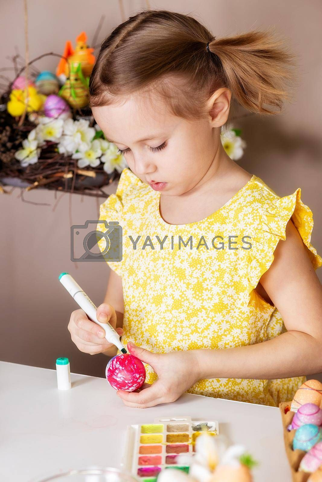 A small girl of 5 years old paints eggs with special markers for Easter. by galinasharapova