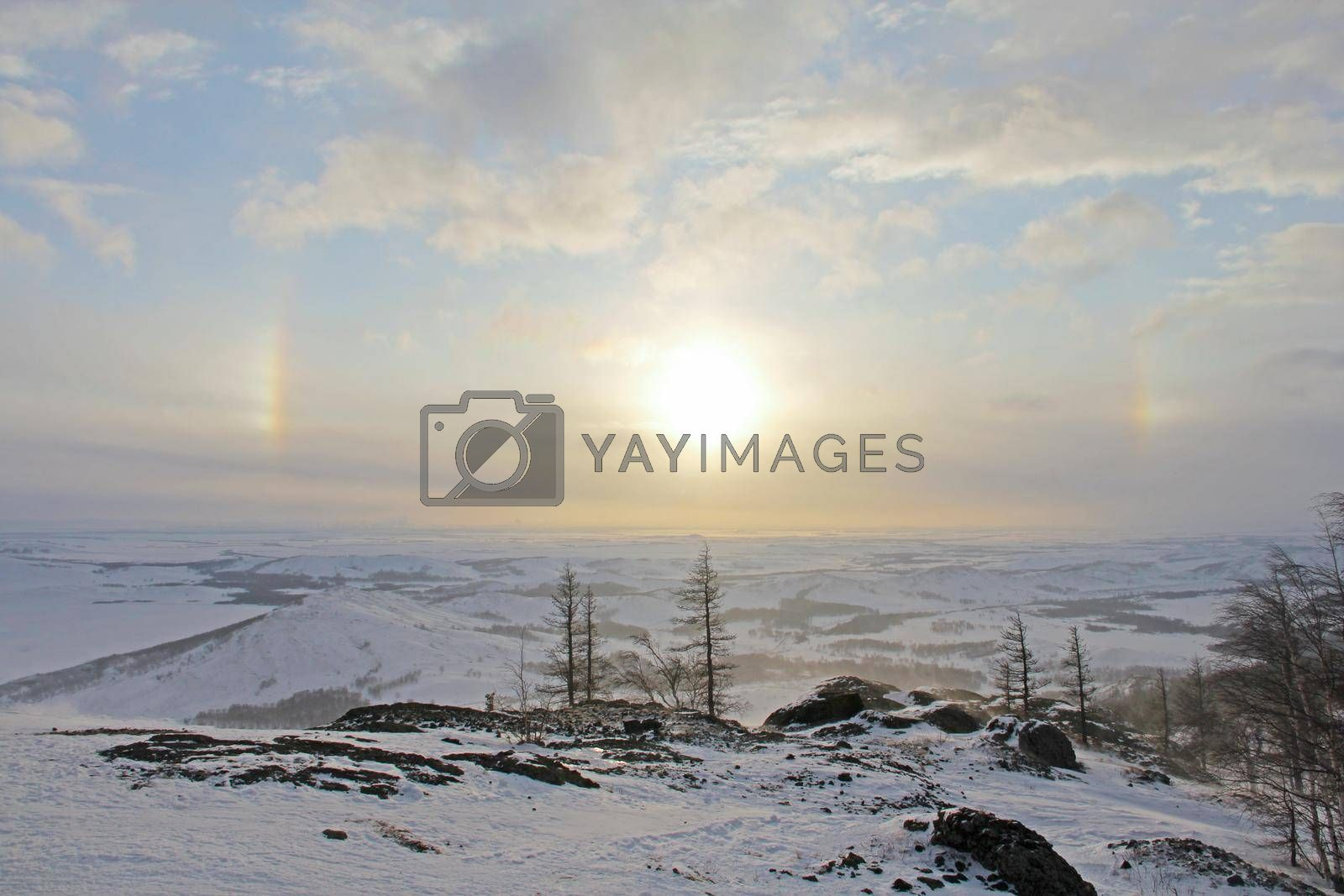 Halo effect over beautiful winter landscape with Lake Bannoe and mountains in snow in South Ural, Russia