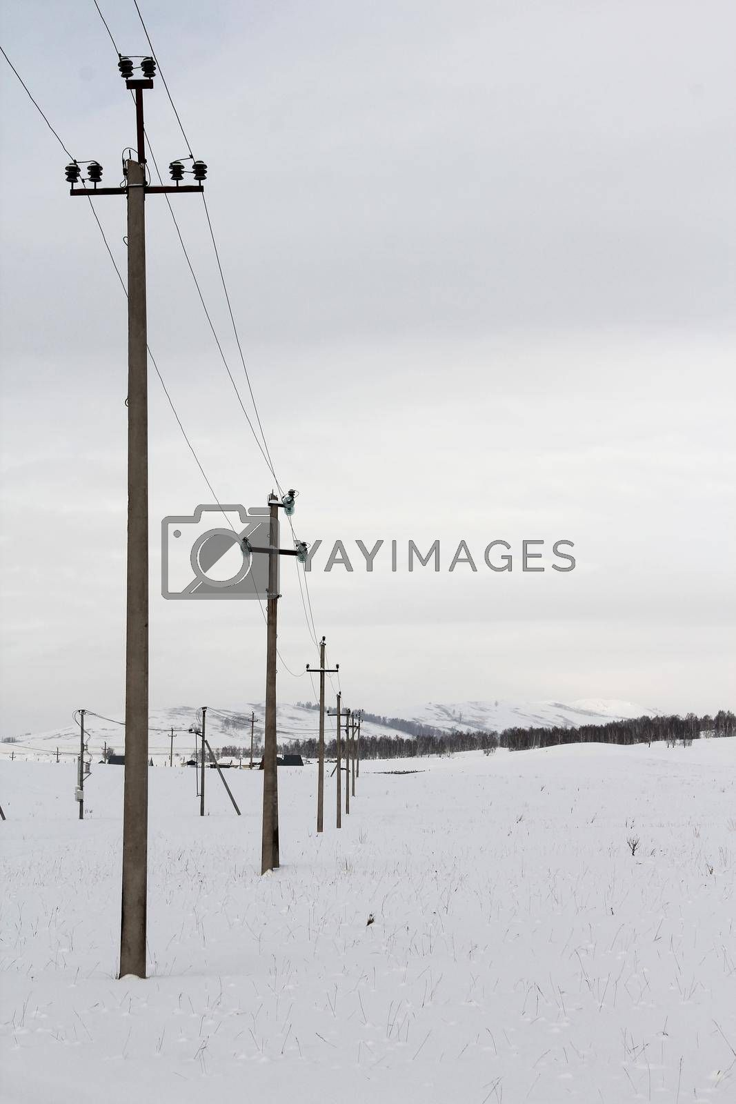 Row of wooden electric poles on empty hilly snow covered landscape. Electrical industry, power line, wiring.