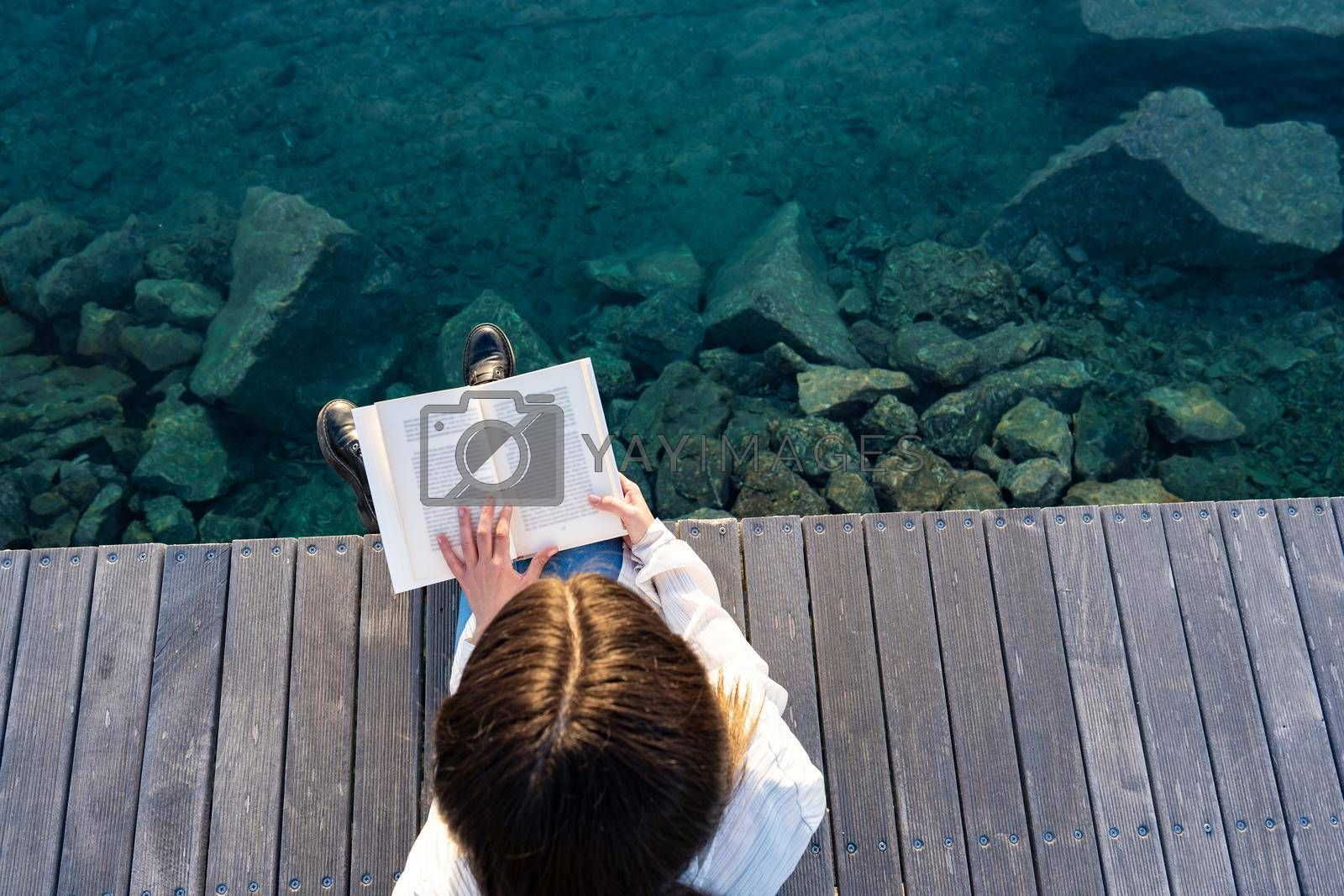 View from top of young school student sitting on a pier on the transparent blue ocean or sea water reading a paper book. Woman relaxing in the nature spends time with her favorite romance novels
