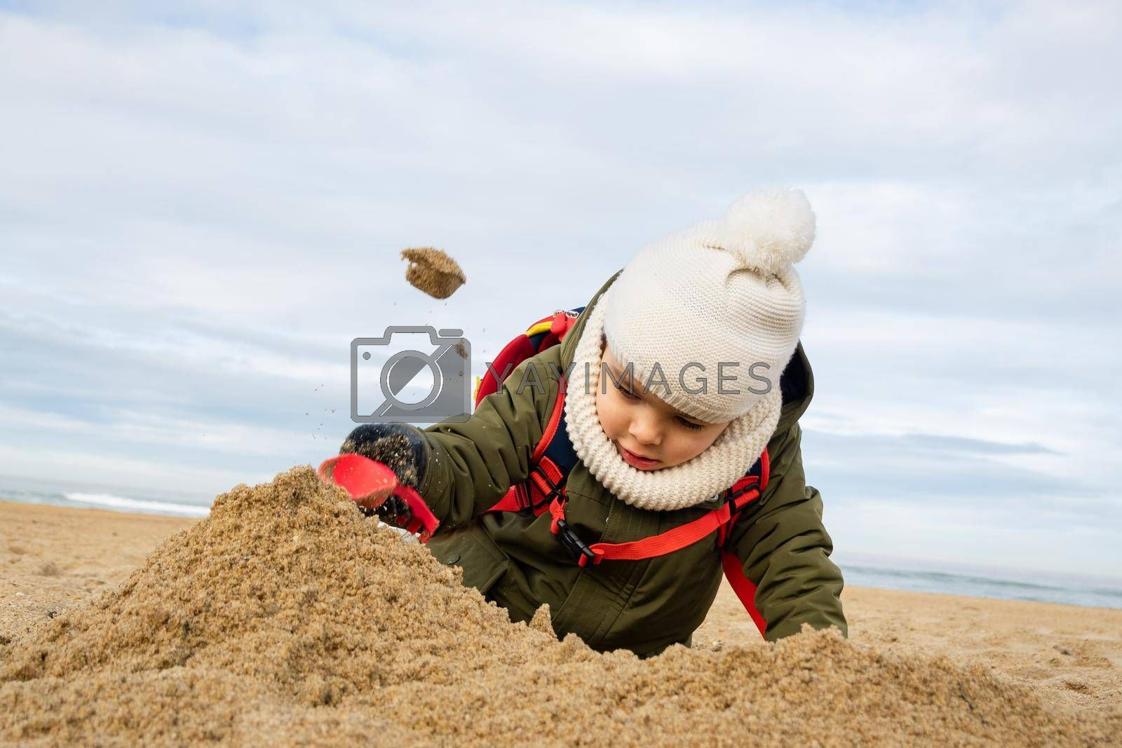 Little boy playing in the sand on beach in winter, toddler throwing sand in the air with small plastic shovel.