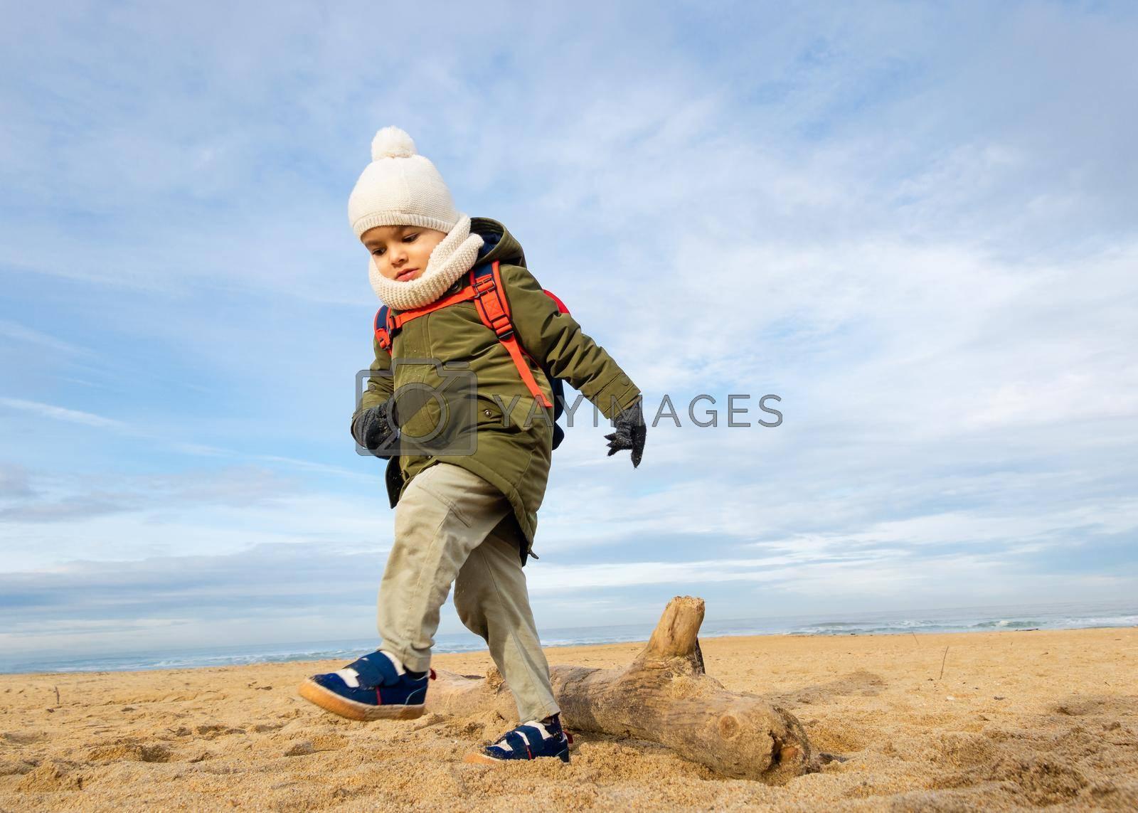 Little boy walking over a log on beach, winter season, low angle shot