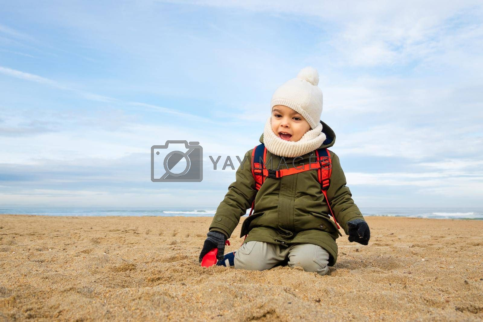 Little boy playing in the sand on beach in winter