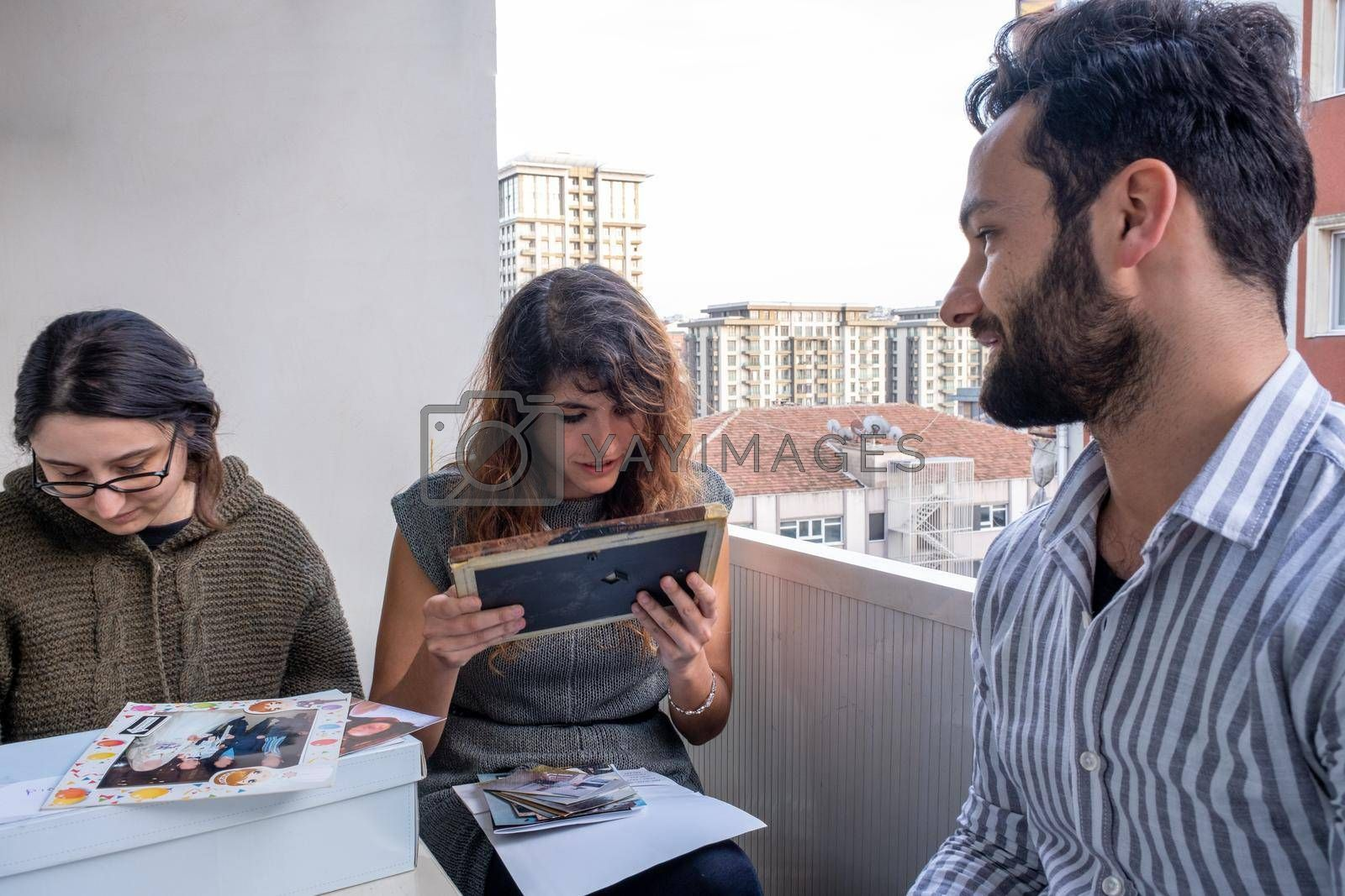 some friends checking photos in a curious way in their balcony at home