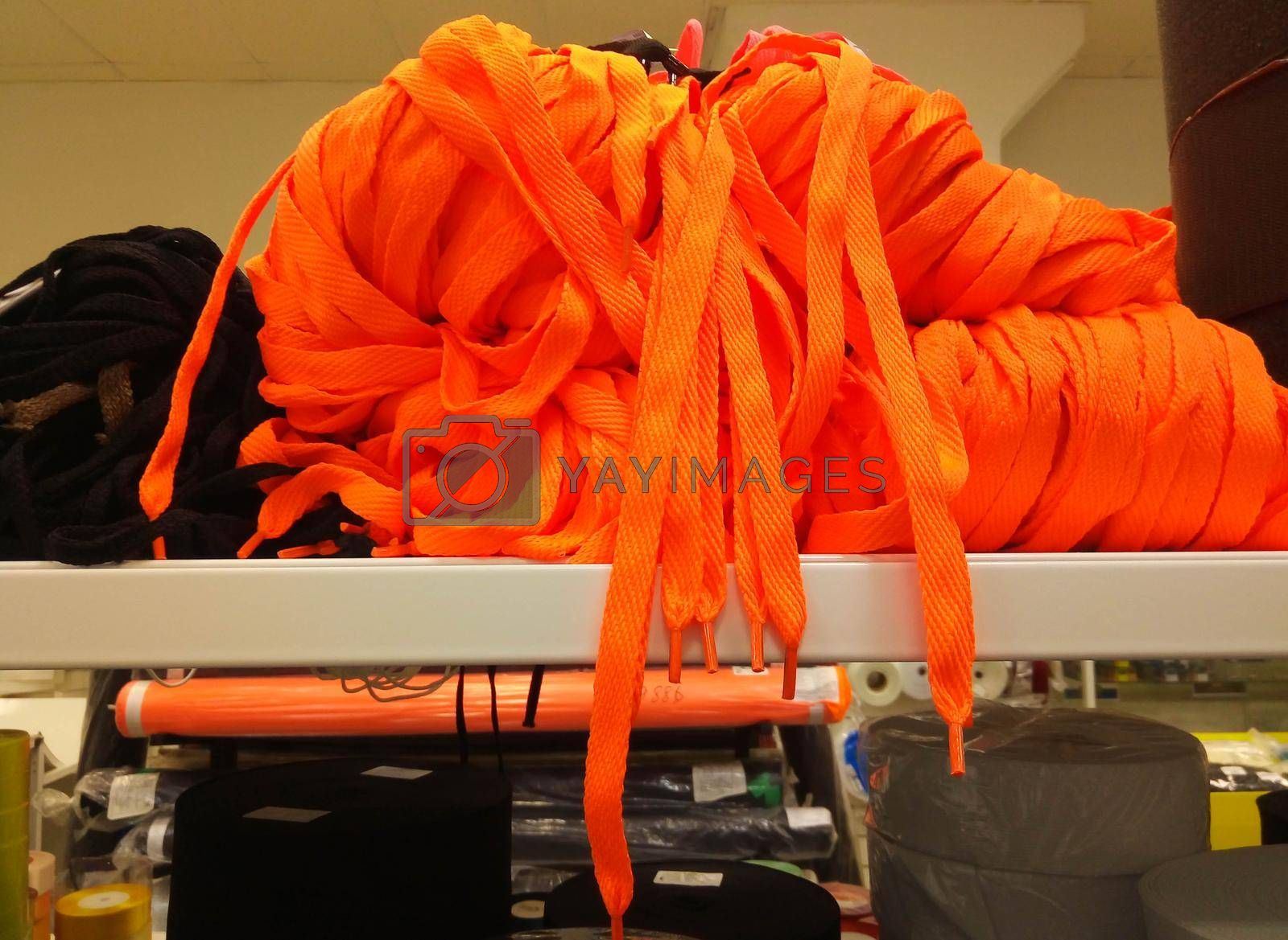 A bunch of orange shoelaces. A bunch of colorful threads for sports shoes, lying on a shelf in the store.
