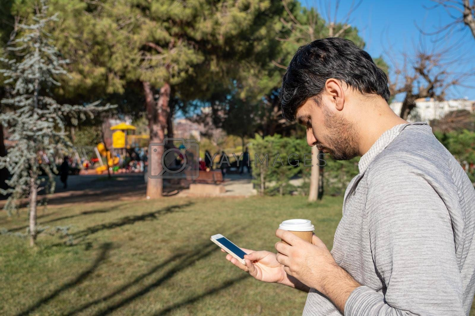 a tall man checks social media on his smart phone in front of green trees with copy space