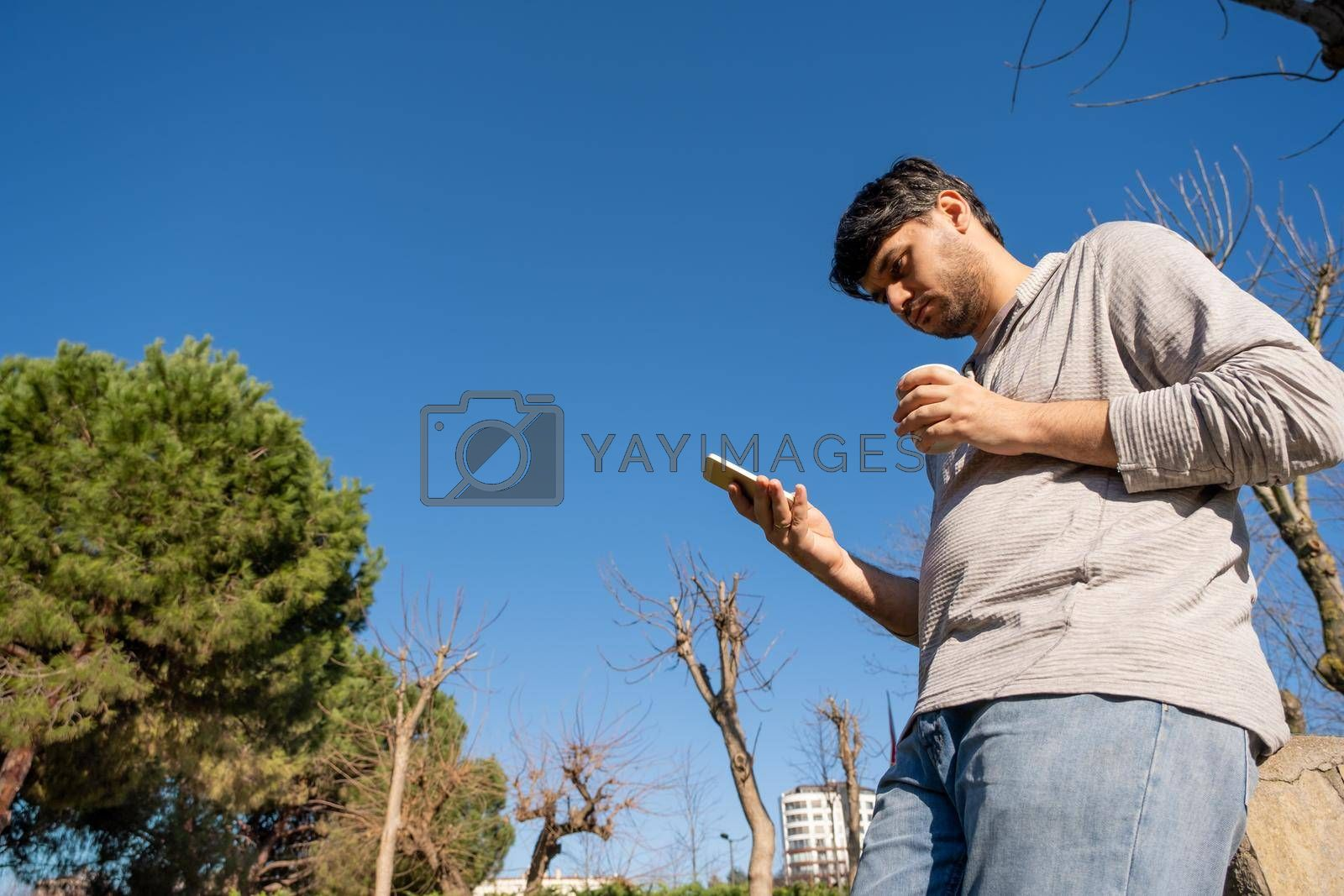 man with white sweatshirt checks his smart phone and holds fresh coffee in an out of focus public park where a lot of trees are around with copy space