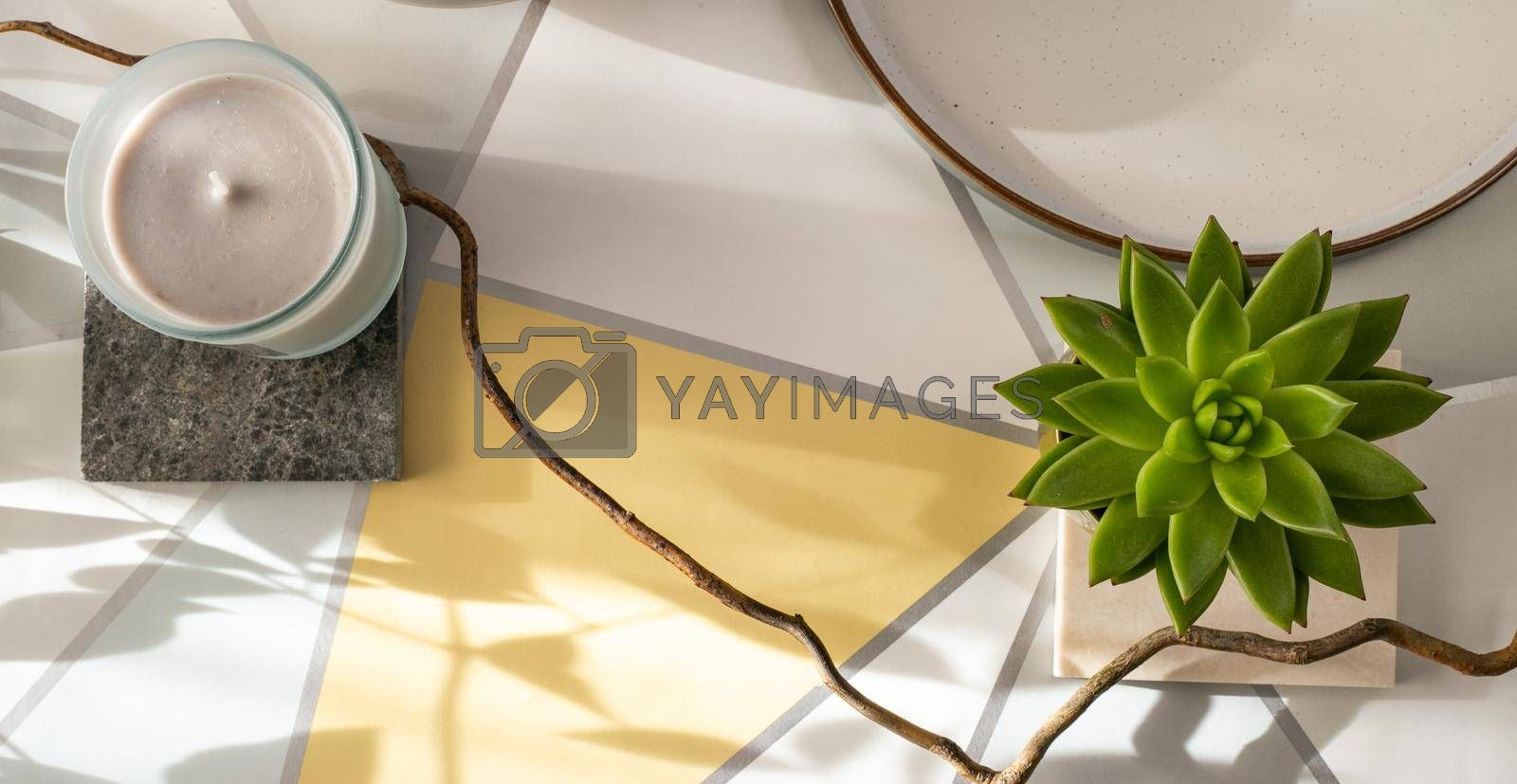 Home plant, candle on pastel yellow grey background. Cosy home with morning sun light, top view. Horizontal flat lay