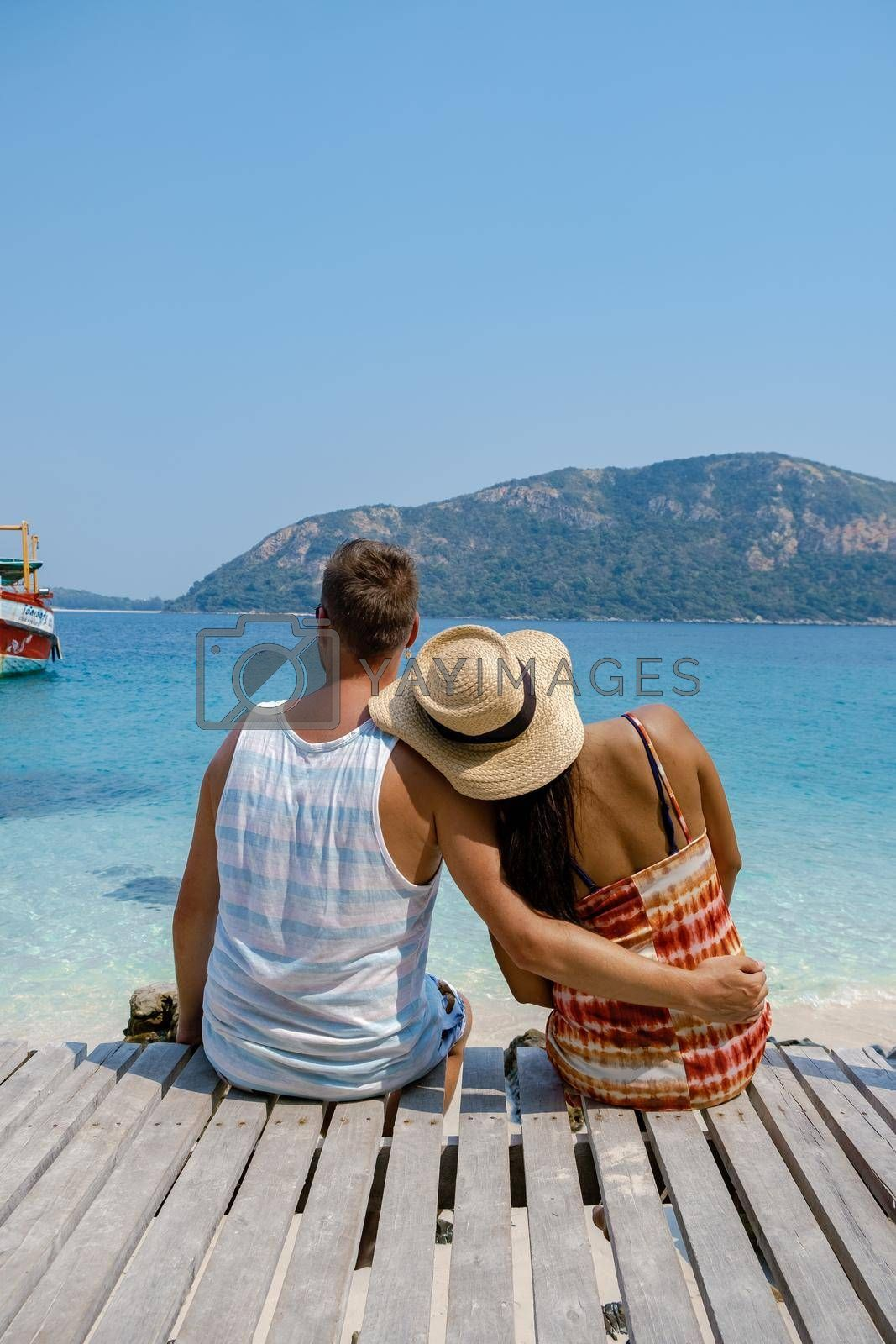 A couple from behind on the backside looking out over the ocean of tropical Island, men and woman vacation, beautiful tropical island beach Koh Kham, Trat Thailand couple relax on tropical Island.