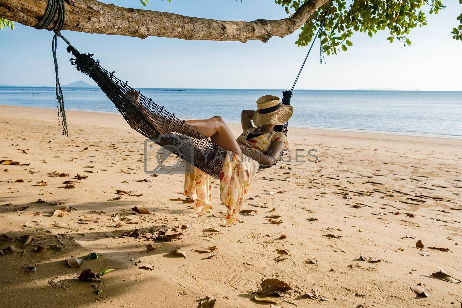 Happy traveler woman in hammock relaxing on the swing and looking beautiful nature, Andaman sea, Krabi, Tourist sea beach Thailand, Asia, Summer holiday vacation travel trip. European man and an Asian woman