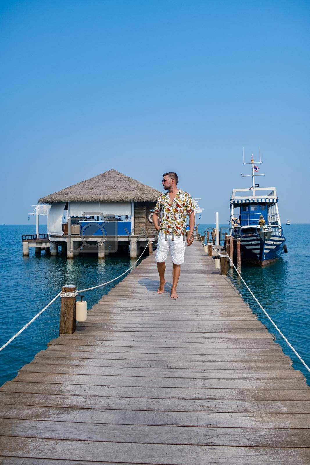 Royalty free image of wooden pier in ocean Pattaya Bangsaray beach Thailand, man walking on wooden pier during vacation Thailand by fokkebok