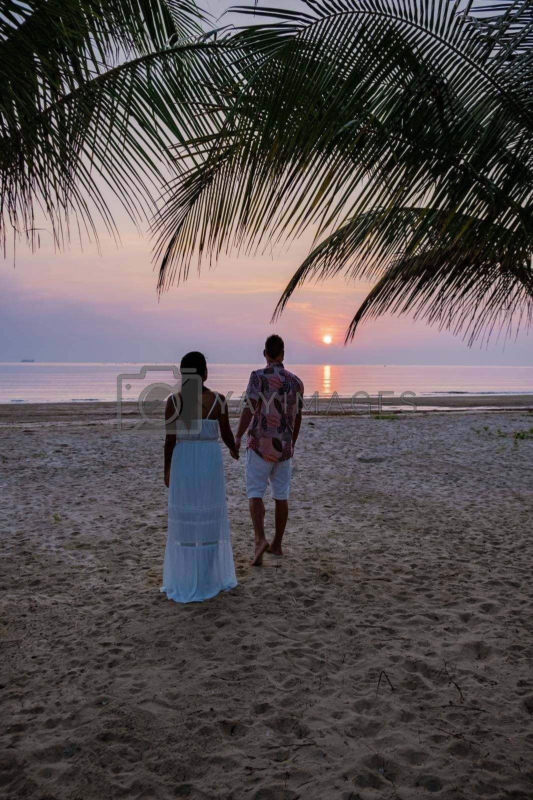 sunrise on the beach with palm trees, Chumphon Thailand, couple watching sunset on the beach in Thailand Asia, mean and woman mid age watching sunrise on beach