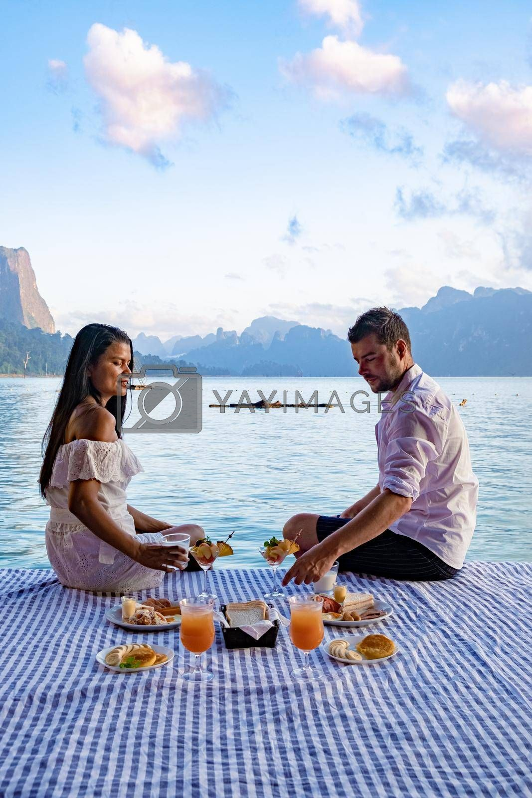 couple having breakfast in front of wooden floating room visiting Khao Sok national park in Phangnga Thailand, Khao Sok National Park, Cheow Lan lake, Ratchaphapha dam. man and woman mid age vacation