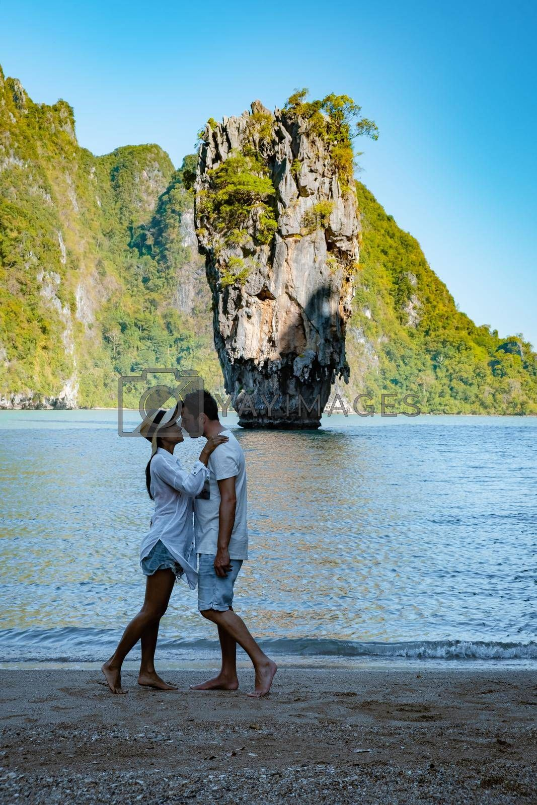 James Bond island near Phuket in Thailand. Famous landmark and famous travel destination, couple men and woman mid age visiting James Bond island in Krabi Thailand. European man and Asian woman on vacation