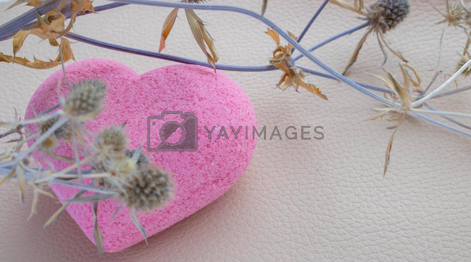 Purple heart bath salt and a dry branch on a beige background. Space for text.