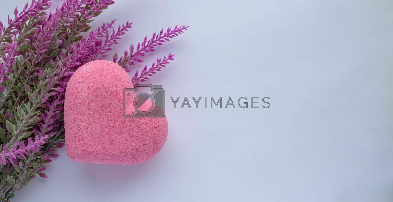 Purple heart bath salt and a branch of artificial lavender on a white background. Space for text.
