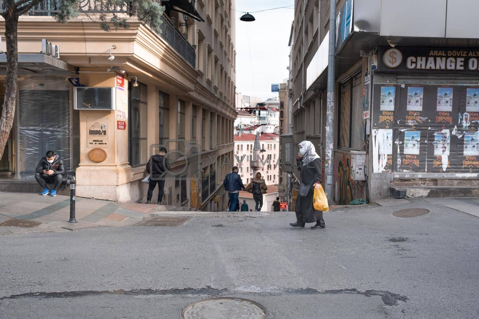 a hijabi woman talking on phone, a man sitting and a couple walking on street