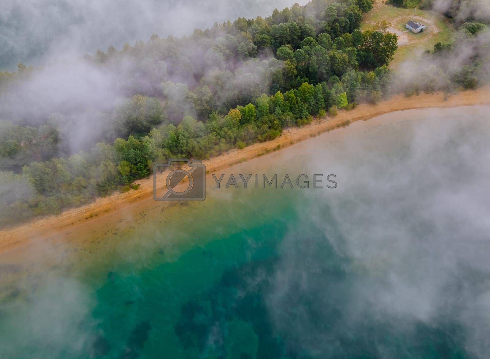 Aerial view of foggy trees in colorful sunrise on autumn landscape with forest low clouds