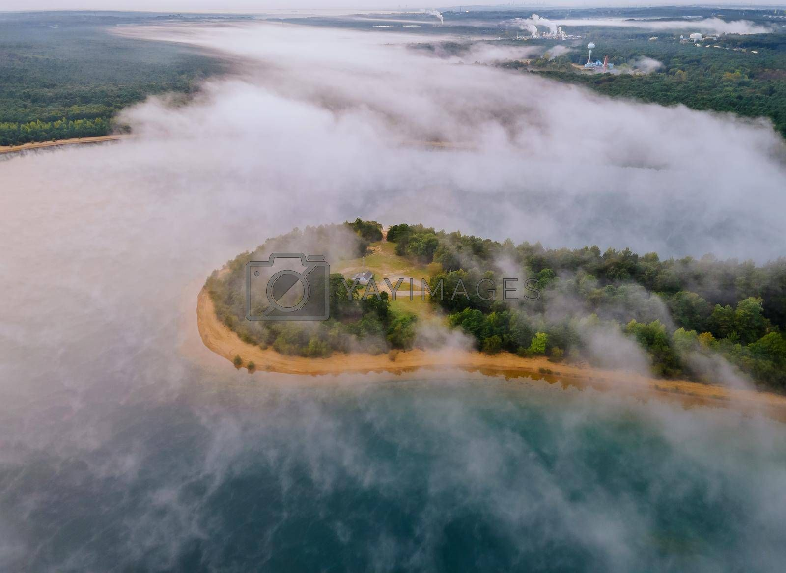 Morning aerial view lake with fog above water surface and sunrise over forest