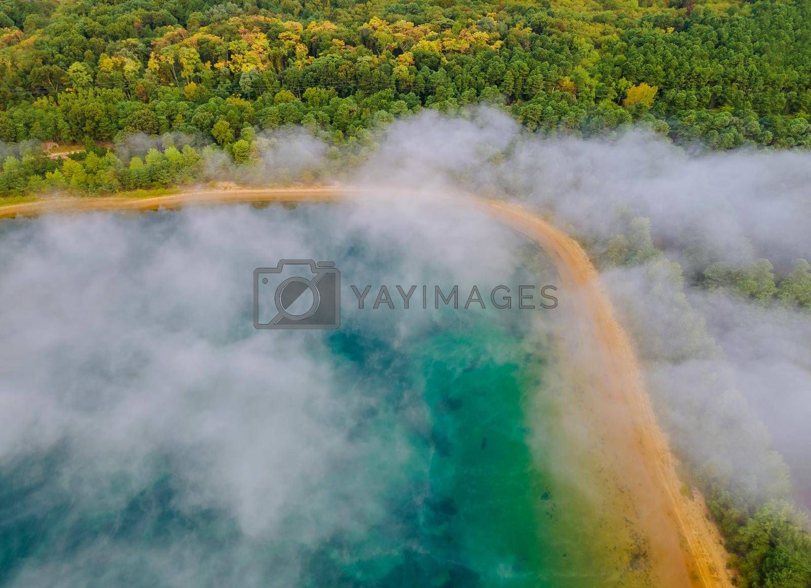 Aerial view of morning mist fog landscape, lake in autumn in the forest blurred fog background