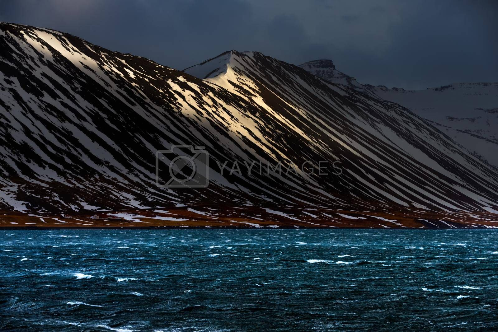 Gorgeous Landscape of a Snow-capped Mountains behind the River. Winter Cold Weather. Amazing Nature of Iceland.