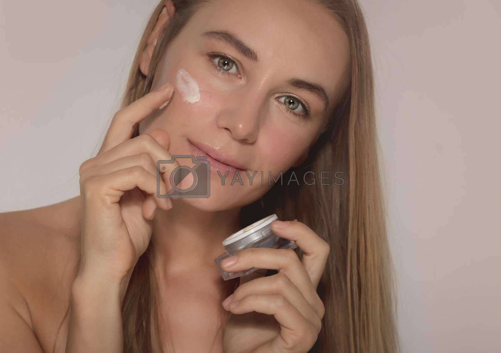 Portrait of a Nice Female Model Using Moisturizing Cream. Isolated on Beige Background. Natural Cosmetics. Beauty and Youthfulness Concept